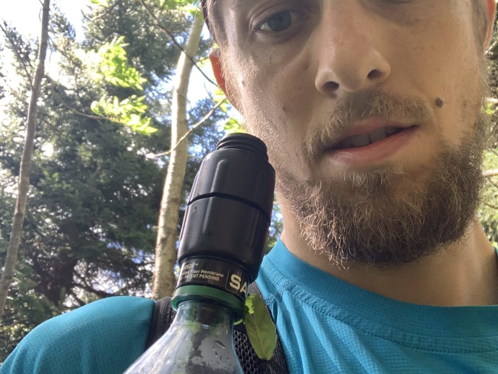 A photo of Joe with a Sawyer watter bottle with a leaf hanging out of it.